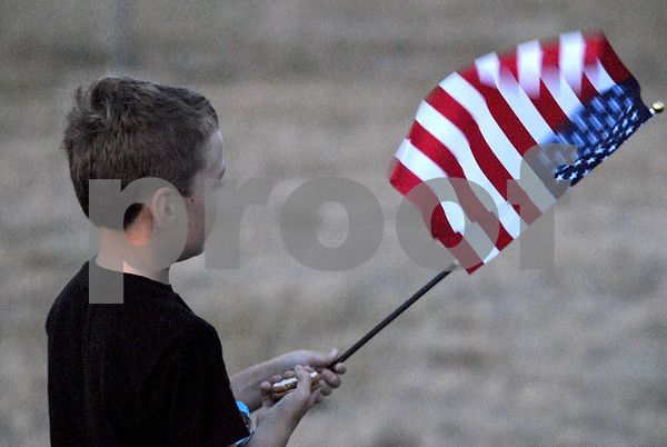 -Messenger photo by Hans Madsen<br /> <br /> Brandon Erpelding, 7, of Algona holds his flag and a pair of cookies Saturday morning while waiting for the Brushy Creek Area Honor Flight to take off from the Fort Dodge Regional Airport. His grandfather, Francis Erpelding, of Burt, was on the flight.