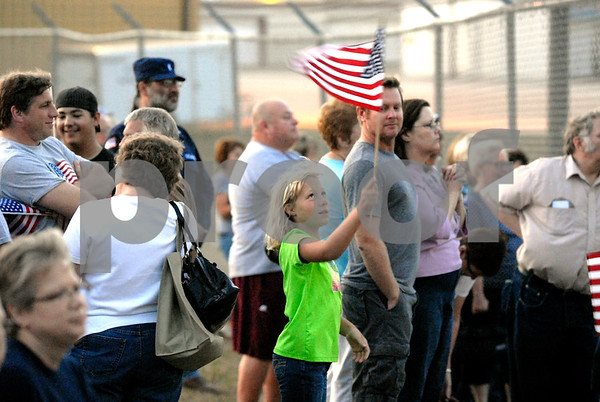 -Messenger photo by Hans Madsen<br /> <br /> Amber Dangelser, 9, of Manson waves her flag Saturday mornning while waiting for the Brushy Creek Area Honor Flight to take off from the Fort Dodge Regional Airpot. Her grandfather, Darrel Freese, of Manson, was on the flight.