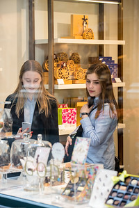 Two girls shopping at the Godiva Belgian chocolate store at Koninklijke Sint-Hubertusgalerijen. The Galeries Royales Saint-Hubert (French) or Koninklijke Sint-Hubertusgalerijen (Dutch) is a glazed shopping arcade in Brussels that preceded other famous 19th-century shopping arcades such as the Galleria Vittorio Emanuele II in Milan and The Passage in St Petersburg. Like them it has twin regular façades with distant origins in Vasari's long narrow street-like courtyard of the Uffizi, Florence, with glazed arcaded shopfronts separated by pilasters and two upper floors, all in an Italianate Cinquecento style, under an arched glass-paned roof with a delicate cast-iron framework.