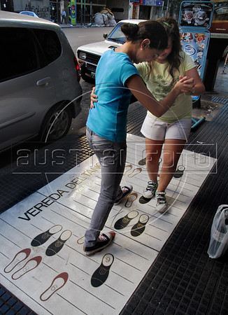 """Two girls try tango steps in a """"Vereda del tango"""" (Walk of tango) in a Buenos Aires street, Buenos Aires, Argentina, January 4, 2009. (Austral Foto/Renzo Gostoli)"""