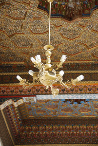The ornate ceiling of the Bakhouddin Nakshbandi mosque, with energy saving bulbs in the chandalier.