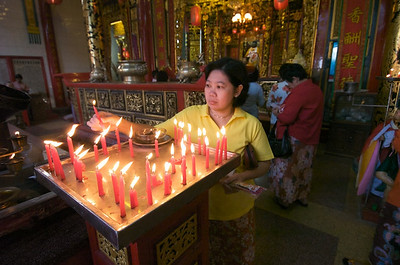 Fairly typical scene: an ethnic chinese woman lights a candle at a buddhist temple in downtown Rangoon. This is done nearly every day by most people. It only takes a few minutes.