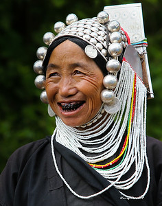 Silver head dress is passed down thru the generations. This lady belongs to a tribe that think animals not people should have white teeth. They blacken the teeth with a plant root.
