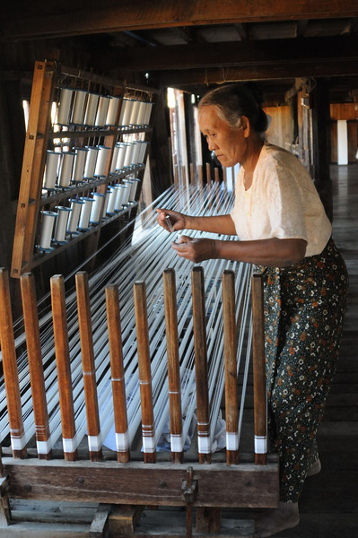 Combining the contents of 30 bobbins of spun thread to produce the final yarn for weaving