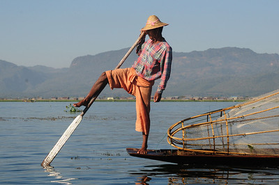 A leg-rower fisherman with his fish trap, Lake Inle, Burma.