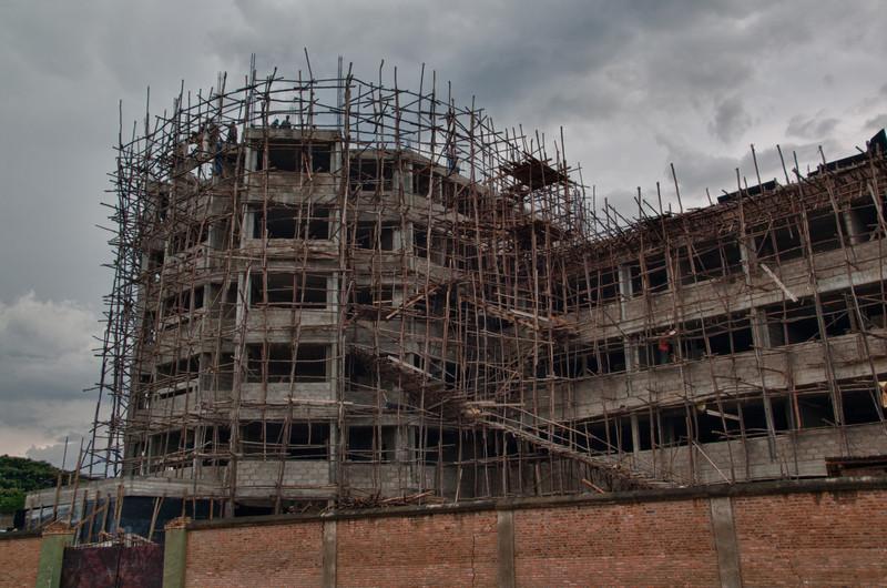 Baustelle in Bujumbura. Da es keine Kräne oder sonstige Baumaschinen gibt werden alle Materialien über die Holzrampe hinaufgetragen.