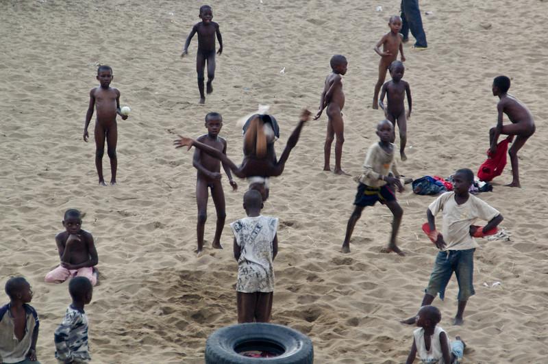 Kinder in Rumonge nutzen einen alten Reifen als Trampolin um Kunststücke vorzuführen.