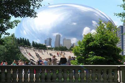 "Cloud Gate is a three-story steel sculpture that has been dubbed ""The Bean"" by Chicagoans, because of its legume-like shape. The sculpture is the first public artwork in the United States by world-renowned artist Anish Kapoor. The privately funded piece cost $23 million, considerably more than the original estimate of $6 million. Composed of 168 stainless steel plates welded together, its highly polished exterior has no visible seams. It is 33×66×42 feet (10×20×13 m) and weighs 110 short tons (100 t; 98 long tons). Cloud Gate is a reflective steel sculpture that is inspired by liquid mercury; the sculpture's surface reflects and distorts the city's skyline. The curved, mirror-like surface of the sculpture provides striking reflections of visitors, the city skyline (particularly the historic Michigan Avenue ""streetwall"") and the sky. Visitors are able to walk around and under Cloud Gate's 12-foot (3.7 m) high arch. On the underside is the ""omphalos"" (Greek for ""navel""), a concave chamber that warps and multiplies reflections. The sculpture builds upon many of Kapoor's artistic themes and is popular with tourists as a photo-taking opportunity for its unique reflective properties. From Wikipedia."