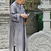High tech monk busy with his cell phone in one hand and holding the counting buddhist bead necklace in the other.