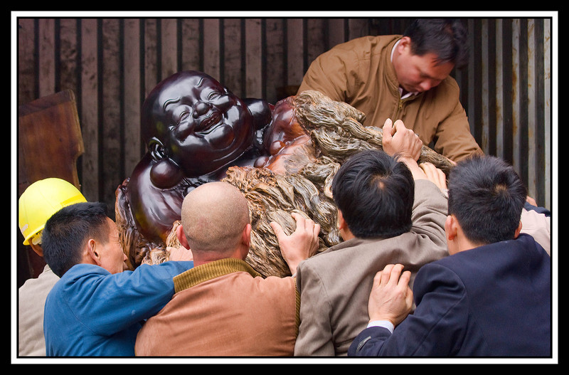 Guilin - Men struggling to lift Buddha statue into truck...