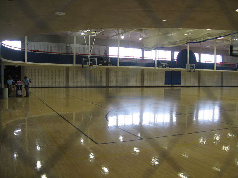 Multiple basketball courts with an indoor running track on the mezzanine above.