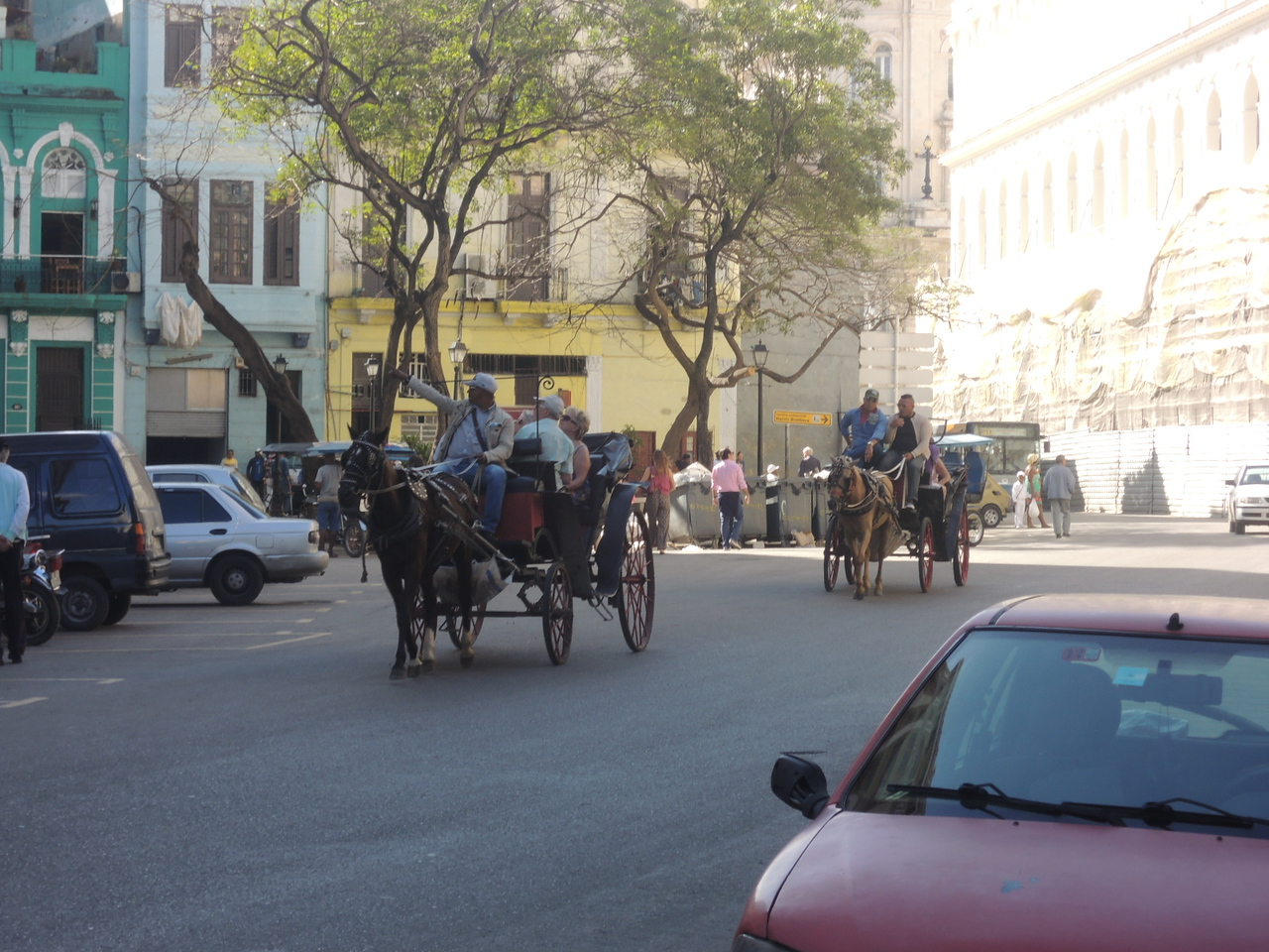 There are many modes of tranportation in Havana.  In this picture you can see horse-drawn carriages, cars, motorcycles, cars, buses, and people walking.