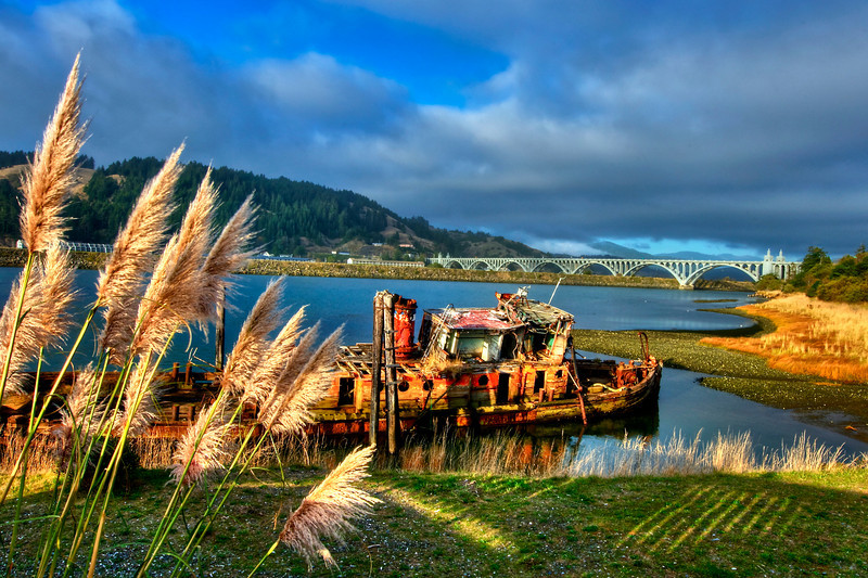 Sunken fishing trawler in Rogue River estuary . Rogue River Bridge in background