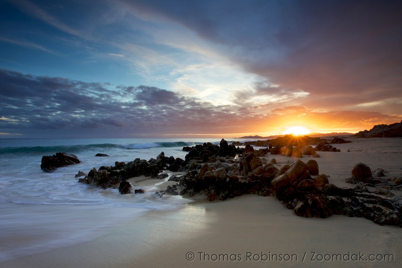 Sunset in Cabo: Waves roll in and around the rocks at sunset on the shores of the Baja Peninsula, Mexico.