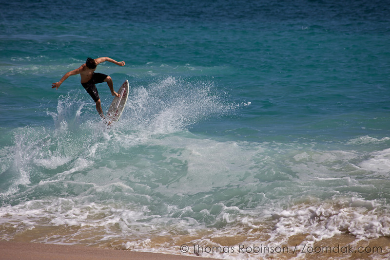 A skim-boarder catches air over a wave along the beach in Cabo, Mexico.