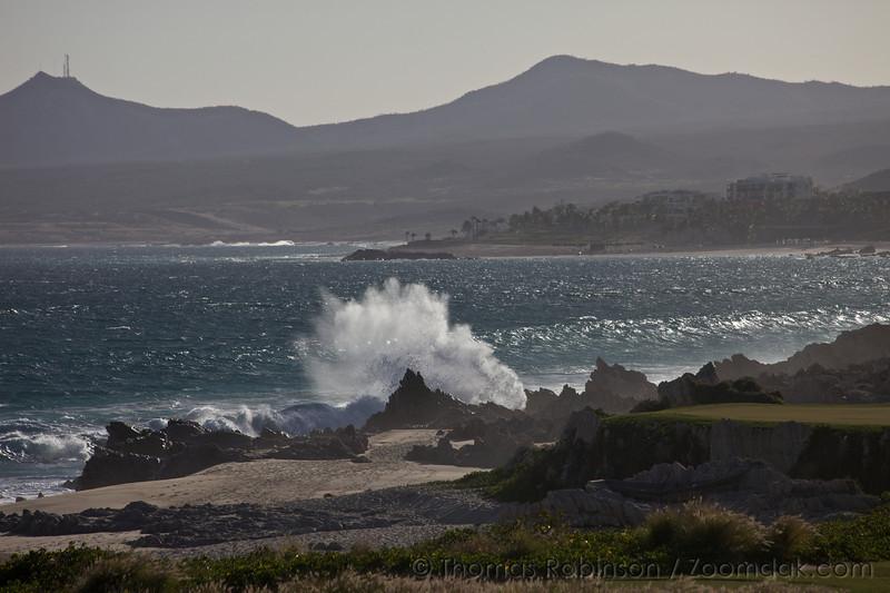 A backlit wave crashes over rocks along the shore of the Baja Peninsula.