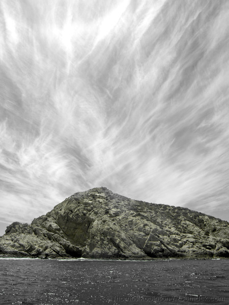 A partially desaturated image shows the cloud patterns above a beach head in Cabo, Mexico,