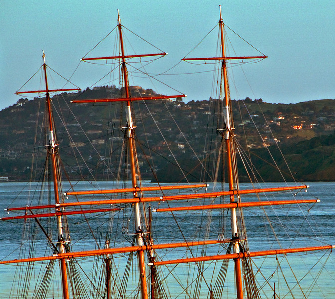 Dawn illuminates the masts and spars of the sailing ship Balcutha moored in the San Francisco Marina---the Berkeley hills are in the background.