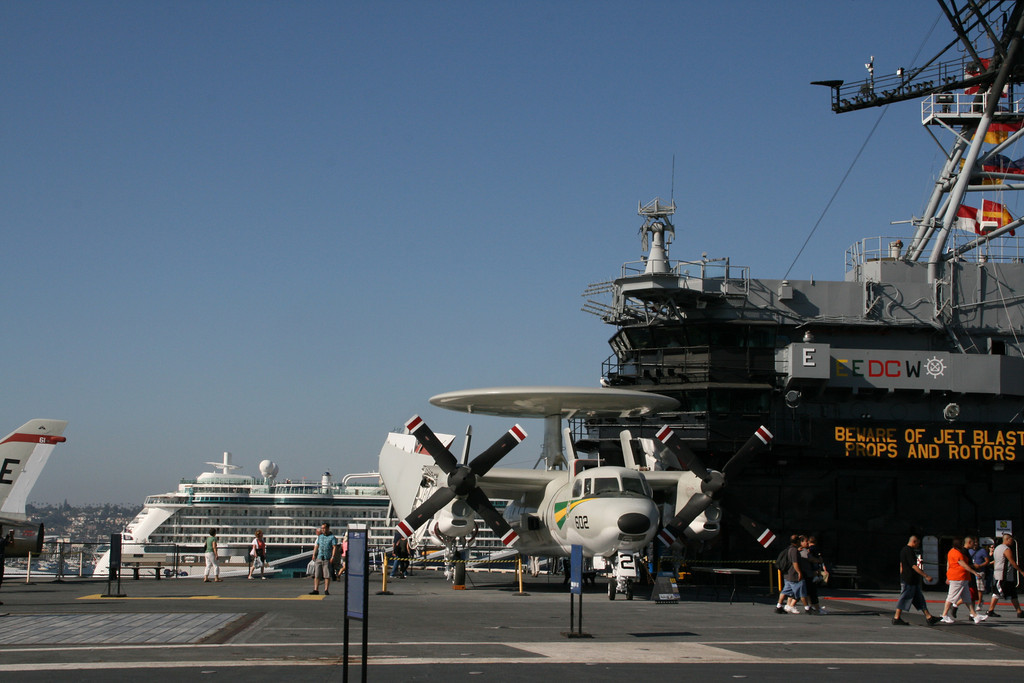 The deck of the USS Midway Museum with a cruise ship in the background - look how small it looks!  It is NOT small, the Midway is huge.