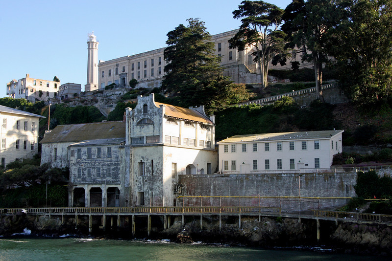 "<b>From left to right --> Guardhouse/Sally Port, Military Chapel aka ""The Chapel"" [no record of it ever being used as a chapel] later used as Bachelor's Quarters, Electric Shop</b><br> <br> During the 1860s, Alcatraz was the most fortified military area on the west coast. A <b>Sally Port</b> is an armored gate. Alcatraz's Sally Port and Guardhouse are the two oldest structures on Alcatraz - built between 1857 and 1859.<br> <br> Formerly, a drawbridge joined the sides of a dry moat so that access could be blocked. The entry way was well guarded with soldiers for anyone making it past the armored gate. The gun rooms were used for prison cells during the Civil War to house captured Confederate agents."