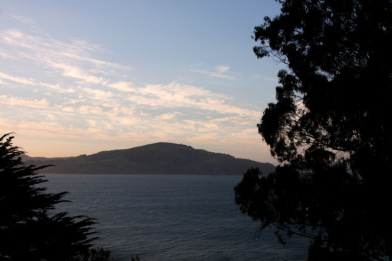 """<b>Angel Island</b> - <b>View from Alcatraz</b><br> <br> The Miwoks used Angel Island for thousands of years before the Spaniards arrived.  Ayala Cove was the staging area for the earliest water-based exploration of the bay area in 1775.   Following many years of Spanish control of the island, it  served as both a military base and the site of two government facilities (Quarantine and Immigration Stations) for nearly 100 years starting in the mid-1800s.  <br> <br> The Miwok had an animistic philosophy:  they wanted no walls and trod lightly on the land, leaving no footsteps, always apologizing to the spirits in animals or nature whenever they disturbed them in whatever fashion.  There is no evidence the Miwok had words for such concepts as war or prostitution.  Their oral history was transmitted through the stories of the elders and shamans.  Tribal boundaries were taught to children by rote.<br> <br> Only temporary houses were built on Angel Island: they did not live there permanently.  Houses were made of branches covered with mats of tule.  Each house had a small acorn house constructed on legs in order to store the acorns they would collect and protect from deer and insects.<br> <br> The Miwoks had no pottery, made no fabric, and planted no seeds.  They kept no domestic animals.  Instead, they were gatherers, fisherman, hunters, and basket makers.  <br> <br> For more detailed information about Angel Island, go <a href=""""http://angelisland.org/history/"""" target=""""_blank""""> <b>here</a></b>."""