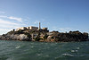 <b>Water Tower</b> [far left], <b>Cellhouse</b>, <b>Lighthouse</b>, and <b>Warden's House</b><br> <br>  Alcatraz was the home of the West Coast's first <b>lighthouse</b>. Equipped with a simple oil lamp, the Alcatraz light began guiding ships through the narrow entrance to the bay in 1854. In 1909, when construction of the cellhouse threatened to block the light beam to the north, the old lighthouse was replaced with the 84-foot tower seen on the island today. The tower's automated rotating light, supplemented by powerful foghorns on either side of the island, continues to be a key navigational aid.<br> <br> Below the Lighthouse was the military Parade Ground. It was surrounded by houses which were later demolished.  [B]