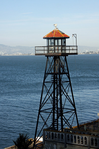 <b>Guard Tower</b><br> <br> Alcatraz's guard towers and catwalks were installed in 1934 - the Federal Penitentiary's first year in operation.  Heavily armed guards kept watch from this tower, plus five others, and a system of catwalks that loomed over the Rock.  <br> <br> The officers used both bullhorns and bullets to warn escape-minded inmates and boats that ventured too near the island.  Warnings worked with inquisitive boaters, but several determined escapees ignored the officers and were either shot or recaptured.  <br> <br> On-duty officers were locked in the towers and connecting sections of catwalk for eight hours, until the next shift.  When the wind blew and the catwalks rocked, patrol above the island could be frightening work.  Assignment was often given to correctional officers new to Alcatraz.