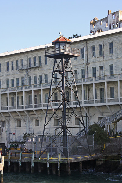 <b>Guard Tower in front of the Barracks aka Building 64</b><br> <br> Alcatraz's guard towers and catwalks were installed in 1934 - the Federal Penitentiary's first year in operation.  Heavily armed guards kept watch from this tower, plus five others, and a system of catwalks that loomed over the Rock.  <br> <br> The officers used both bullhorns and bullets to warn escape-minded inmates and boats that ventured too near the island.  Warnings worked with inquisitive boaters, but several determined escapees ignored the officers and were either shot or recaptured.  <br> <br> On-duty officers were locked in the towers and connecting sections of catwalk for eight hours, until the next shift.  When the wind blew and the catwalks rocked, patrol above the island could be frightening work.  Assignment was often given to correctional officers new to Alcatraz.