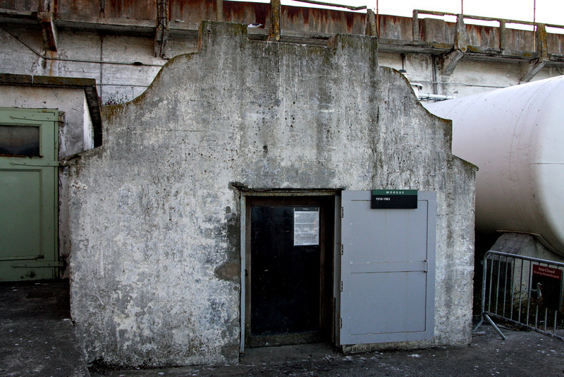 <b>Morgue</b><br> <br> Originally, this site was the entrance to an 1870s tunnel used by soldiers to cross to the opposite side of the island. In 1910, the Army built a morgue inside, which contained three vaults and an examination table.  <br> <br> Deceased army personnel from Alcatraz were buried in the military cemetary on Angel Island. When the burial ground was closed in the early 1900s, funerals were conducted at the National Cemetary in the Presidio of San Francisco.<br> <br> This small structure had a stell door, a grated skylight, and now - a dank and mossy examination table. This morgue had only one documented use - overnight storage of the body of a prisoner who died after the last boat run.  <br> <br> No autopsies were performed there. All deceased inmates were brought back to the mainland and released to the San Francisco County Coroner.