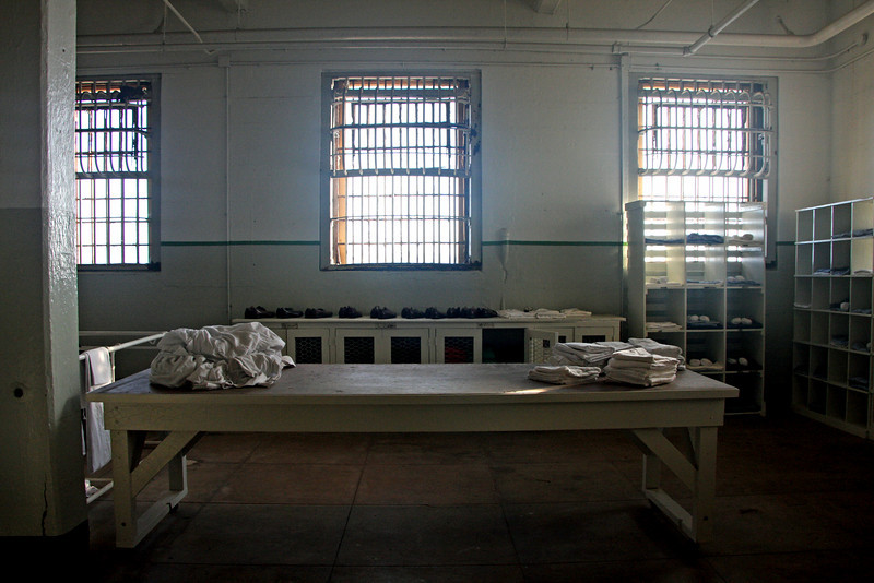 <b>Clothing Room</b><br> <br> The grim process of the first day at Alcatraz began here where convicts were issued their clothing, a prison uniform with an identification number. From here, new prisoners were escorted to their cells.<br> <br> The standard inmate uniform for all normal activities inside the cellhouse consisted of blue chambray shirt, Blue and White (B&W) trousers, web waist belt, and issue shoes.<br> <br> This uniform was worn at visits, interviews, meals, movies, etc. The shirt was to be buttoned except for the top collar button. The sleeves were to be rolled down and buttoned. The belt was to be worn with the inmate's  register number in plain view, at the center of their back.<br> <br> There were required to wear this standard uniform to and from outside work or the Recreation Yard, but the could  add to it a cap, jacket, coat or raincoat. The inmates could wear tennis shoes to the Recreation Yard only. They were to wear a robe and slippers or shoes when going to and from bath.<br> <br> They were not allowed to change or alter any of the issue clothing and were to keep the clothing neat, clean and in good repair at all times.<br> <br> Special work clothing was issued for work details. This special clothing was kept at the place of work and was not to be brought to the Yard or cellhouse.<br> <br> Culinary inmates wore a special work uniform consisting of white cap, white shirt and white pants. This uniform was issued for work only but was worn between the cell and Culinary Unit. Culinary workers were cautioned to wear their complete uniform with all buttons except the top collar button fastened before leaving their cells to go to work.