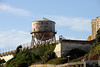 <b>Water Tower</b><br> <br> A 250,000 gallon water tower was built in 1939. The water was used for drinking, firefighting, and laundry.<br> <br> The recreation yard was to the right of the water tower - sourrounded by the barbed wire.