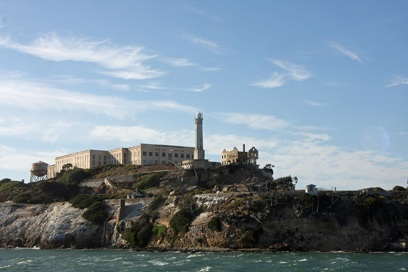<b>Water Tower</b> [far left], <b>Cellhouse</b>, <b>Lighthouse</b>, and <b>Warden's House</b><br> <br>  Alcatraz was the home of the West Coast's first <b>lighthouse</b>. Equipped with a simple oil lamp, the Alcatraz light began guiding ships through the narrow entrance to the bay in 1854. In 1909, when construction of the cellhouse threatened to block the light beam to the north, the old lighthouse was replaced with the 84-foot tower seen on the island today. The tower's automated rotating light, supplemented by powerful foghorns on either side of the island, continues to be a key navigational aid.<br> <br> Below the Lighthouse was the military Parade Ground. It was surrounded by houses which were later demolished.