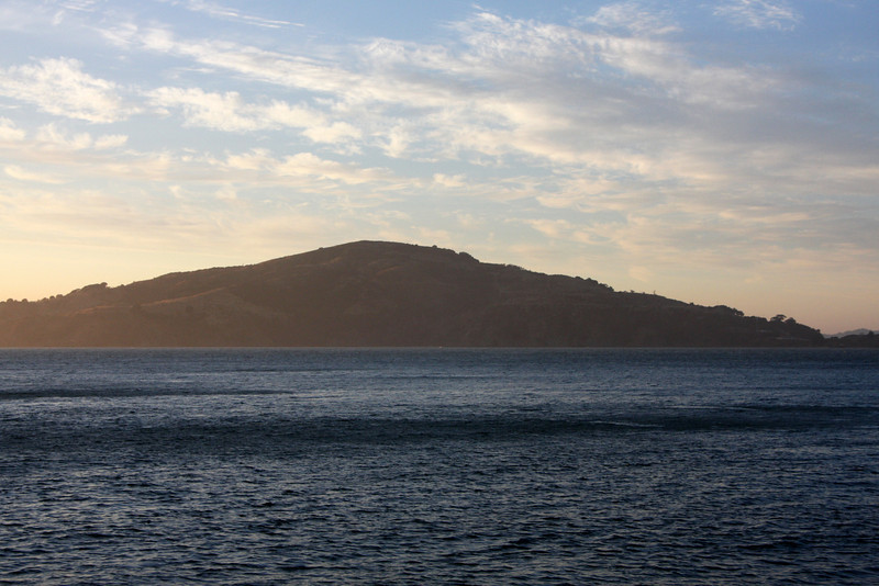 """<b>Angel Island</b> - <b>View from Alcatraz</b><br> <br> The Miwoks used Angel Island for thousands of years before the Spaniards arrived.  Ayala Cove was the staging area for the earliest water-based exploration of the bay area in 1775.   Following many years of Spanish control of the island, it  served as both a military base and the site of two government facilities (Quarantine and Immigration Stations) for nearly 100 years starting in the mid-1800s.  <br> <br> The Miwok had an animistic philosophy:  they wanted no walls and trod lightly on the land, leaving no footsteps, always apologizing to the spirits in animals or nature whenever they disturbed them in whatever fashion.  There is no evidence the Miwok had words for such concepts as war or prostitution.  Their oral history was transmitted through the stories of the elders and shamans.  Tribal boundaries were taught to children by rote.<br> <br> Only temporary houses were built on Angel Island: they did not live there permanently.  Houses were made of branches covered with mats of tule.  Each house had a small acorn house constructed on legs in order to store the acorns they would collect and protect from deer and insects.<br> <br> The Miwoks had no pottery, made no fabric, and planted no seeds.  They kept no domestic animals.  Instead, they were gatherers, fisherman, hunters, and basket makers.  <br> <br> For more detailed information about Angel Island, go <a href=""""http://www.angelisland.org/historic2.htm"""" target=""""_blank""""> <b>here</a></b>."""