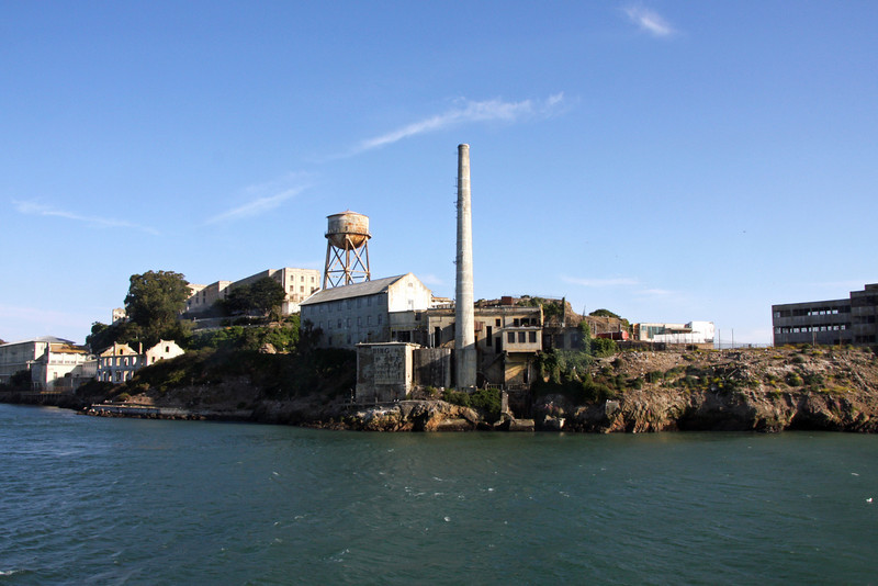 <b>Alcatraz</b> - <b>Power House (foreground) and Quartermaster Warehouse (three-story building immediate left)</b><br> <br> Like more than two-thirds of Alcatraz, the power house area was off-limit to prisoners. This did not stop Frank Morris and the Anglin brothers from passing through it in 1962 as they crept down the slick sides of the Rock and began a probably ill-fated swim to freedom. The preparations for the break had been elaborate: they had fashioned tools out of spoons and fans, molded plaster heads to fool the guards into thinking that they were still in their cells sleeping, and built a life raft out of raincoats. On this flimsy craft they wagered their lives. Though the only trace of them ever found was a wallet belonging to Clarence Anglin washed up on nearby Angel Island, many prefer to believe that they made it. The names of Morris and the Anglins live on in Alcatraz folklore, replacing the names of Cole and Roe in many anecdotes and sighting reports.