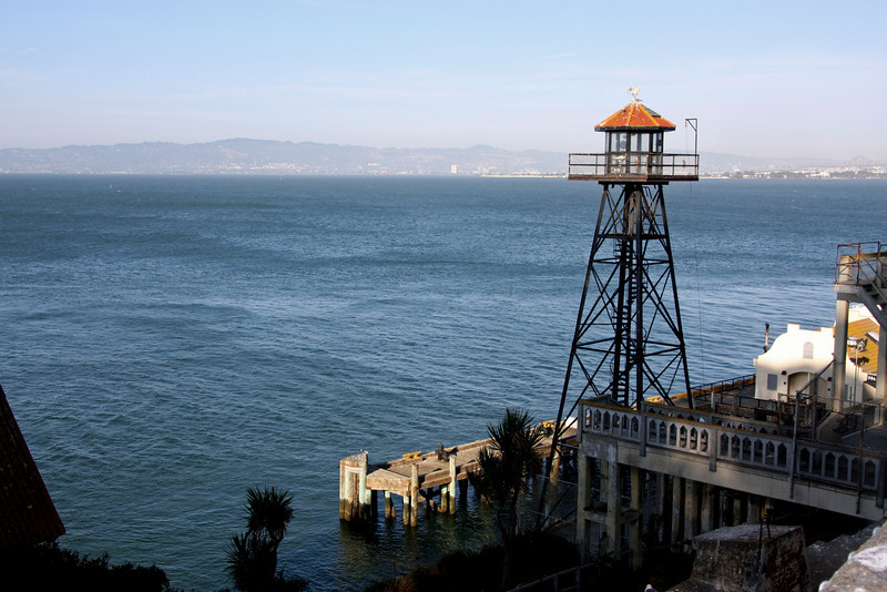 <b>Guard Tower</b><br> <br> Alcatraz's guard towers and catwalks were installed in 1934 - the Federal Penitentiary's first year in operation.  Heavily armed guards kept watch from this tower, plus five others, and a system of catwalks that loomed over the Rock.  <br> <br> The officers used both bullhorns and bullets to warn escape-minded inmates and boats that ventured too near the island.  Warnings worked with inquisitive boaters, but several determined escapees ignored the officers and were either shot or recaptured.  <br> <br> On-duty officers were locked in the towers and connecting sections of catwalk for eight hours, until the next shift.  When the wind blew and the catwalks rocked, patrol above the island could be frightening work.  Assignment was often given to correctional officers new to Alcatraz. [B]