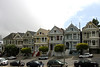 "<b>Painted Ladies</b> is a term used for Victorian and Edwardian houses and buildings painted in three or more colors that embellish or enhance their architectural details. The term was first used for San Francisco Victorian houses by writers Elizabeth Pomada and Michael Larsen in their 1978 book <i>Painted Ladies - San Francisco's Resplendent Victorians</i>.<br> <br> In 1963, San Francisco artist Butch Kardum began combining intense blues and greens on the exterior of his Italianate-style Victorian House. His house was criticized by some, but other neighbors began to copy the bright colors on their own houses. Kardum became a color designer, and he and other artists such as Tony Cataletich, Bob Buckter, and Jazon Wonders began to transform dozens of gray houses into Painted Ladies. By the 1970s, the colorist movement, as it was called, had changed entire streets and neighborhoods. This process continues to this day.<br> <br> About 48,000 houses in the Victorian and Edwardian styles were built in San Francisco between 1849 and 1915 (with the change from Victorian to Edwardian occurring on the death of Queen Victoria in 1901), and many were painted in bright colors. As one newspaper critic noted in 1885, ""...red, yellow, chocolate, orange, everything that is loud is in fashion...if the upper stories are not of red or blue... they are painted up into uncouth panels of yellow and brown...""<br> <br> One of the best-known groups of ""Painted Ladies"" is the row of Victorian houses at 712–720 Steiner Street, bordering Alamo Square park, in San Francisco. It is sometimes known as ""Postcard Row."" The houses were built between 1892 and 1896 by developer Matthew Kavanaugh, who lived next door in the 1892 mansion at 722 Steiner Street (the Shannon-Kavanaugh House shown in previous photos)."