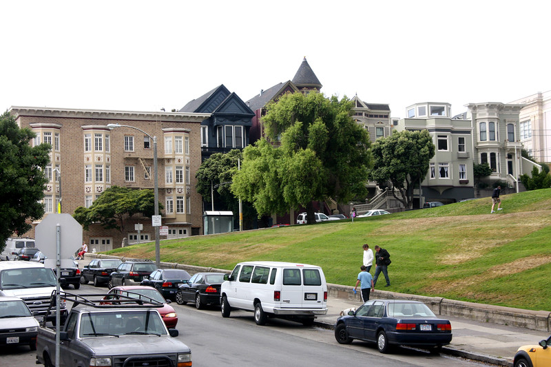 """<b>Alamo Square</b> is a residential neighborhood and park.  It consists of four city blocks at the top of a hill overlooking much of San Francisco, with a number of large and architecturally distinctive mansions along the perimeter.<br> <br> A row of Victorian houses facing the park on Steiner Street, known as the """"Painted Ladies,"""" are often shown in the foreground of panoramic pictures of the city's downtown area. On a clear day, the Transamerica Pyramid building and the tops of the Golden Gate Bridge and Bay Bridge can be seen from the park's center.  [B]"""