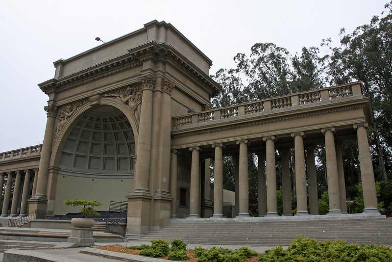 """<b>Music Concourse in Golden Gate Park</b> is a sunken, oval-shaped open-air plaza originally excavated for the California Midwinter International Exposition of 1894. Its focal point is the Spreckels Temple of Music, also called the """"Bandshell"""" where numerous music performance have been staged. It includes a number of statues of various historic figures, four fountains, and a regular grid array of heavily pollarded trees."""