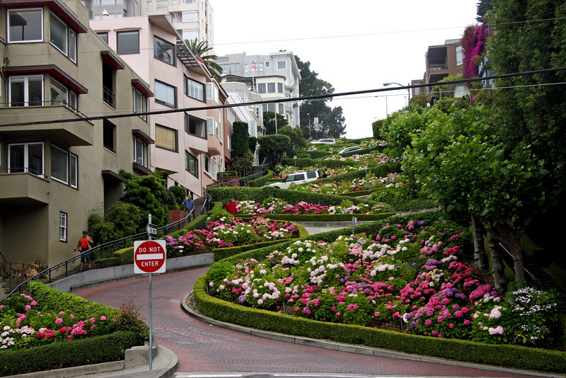 "<b>Lombard Street</b> is best known for the one-way section on Russian Hill between Hyde and Leavenworth Streets in which the roadway has eight sharp turns (or switchbacks) that have earned the street the distinction of being ""the crookedest [most winding] street in the world."" The switchbacks' design, first suggested by property owner Carl Henry and instituted in 1922 was born out of necessity in order to reduce the hill's natural 27% grade, which was too steep for most vehicles to climb. <br> <br> It is also a serious hazard to pedestrians, who are accustomed to a more reasonable sixteen-degree incline. The crooked section of the street, which is about 1/4 mile (400 m) long, is reserved for one-way traffic traveling east (downhill) and is paved with red bricks. The speed limit in this section is a mere 5 mph (8 km/h).<br> <br> In the 1950s, the street was gardened by a Frenchmen who owned the Bercut meat market.<br> <br> Some of the classiest and most expensive Real Estate in the city, exists on Lombard Street. This Russian Hill neighborhood, somehow possesses stately mansions, condos and townhouses, even with the endless array of tourists pouring down the street every day.<br> <br> Lombard Street is not only ""The Crooked Street."" It continues in both directions, going all the way east, up Telegraph Hill to Coit Tower and continues west down through the Marina, where it becomes the major conduit to Golden Gate Bridge. A walk in either direction makes for a pleasant hike. [B]"