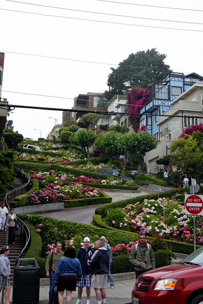 "<b>Lombard Street</b> is best known for the one-way section on Russian Hill between Hyde and Leavenworth Streets in which the roadway has eight sharp turns (or switchbacks) that have earned the street the distinction of being ""the crookedest [most winding] street in the world."" The switchbacks' design, first suggested by property owner Carl Henry and instituted in 1922 was born out of necessity in order to reduce the hill's natural 27% grade, which was too steep for most vehicles to climb. <br> <br> It is also a serious hazard to pedestrians, who are accustomed to a more reasonable sixteen-degree incline. The crooked section of the street, which is about 1/4 mile (400 m) long, is reserved for one-way traffic traveling east (downhill) and is paved with red bricks. The speed limit in this section is a mere 5 mph (8 km/h).<br> <br> In the 1950s, the street was gardened by a Frenchmen who owned the Bercut meat market.<br> <br> Some of the classiest and most expensive Real Estate in the city, exists on Lombard Street. This Russian Hill neighborhood, somehow possesses stately mansions, condos and townhouses, even with the endless array of tourists pouring down the street every day.<br> <br> Lombard Street is not only ""The Crooked Street."" It continues in both directions, going all the way east, up Telegraph Hill to Coit Tower and continues west down through the Marina, where it becomes the major conduit to Golden Gate Bridge. A walk in either direction makes for a pleasant hike."