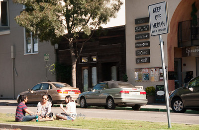 People sit on a grass meridean in Berkely, despite a Keep Off Meridian sign.