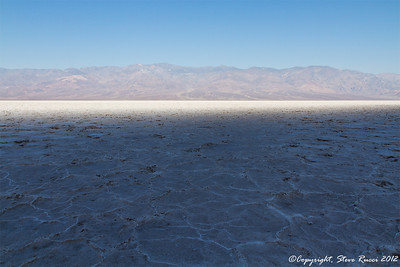 Out on the salt flat at Badwater Basin in Death Valley National Park, California.  The shade from the hills behind me is quickly vanishing, revealing sun and bright reflections.  I was rapidly retreating from this, because the high temperature on this day was 120 degrees.  Standing on the salt flat in such conditions is like being in a frying pan.