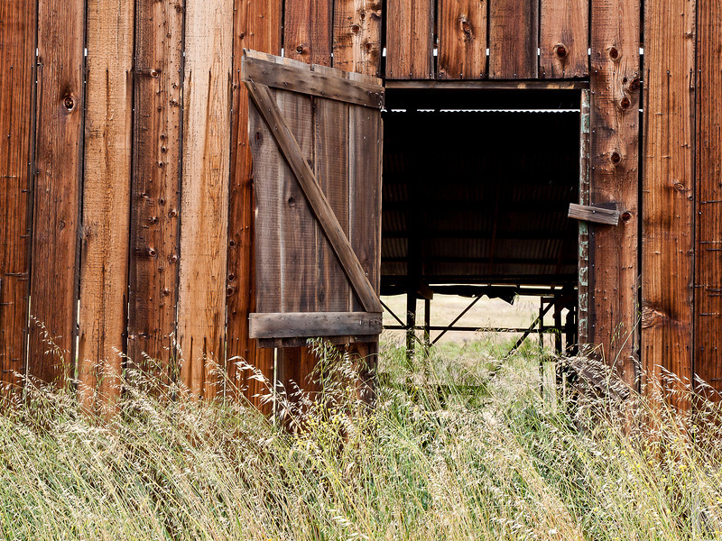 A barn door swings in the wind in Soledad, CA