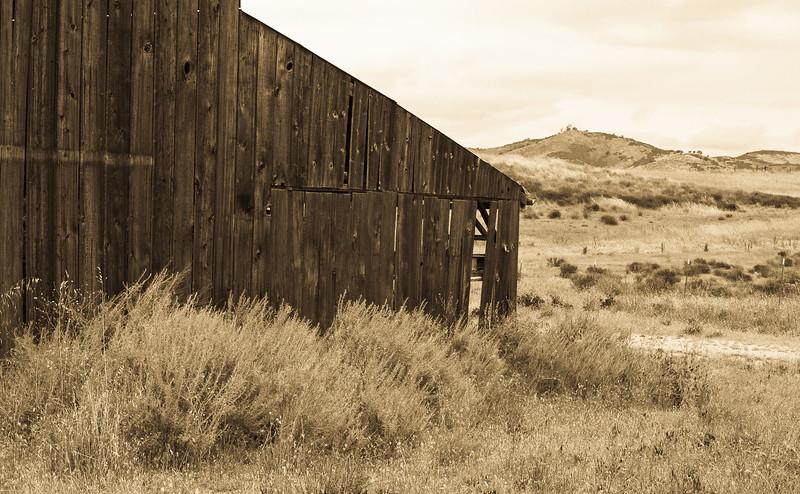 an abandon barn ponders the hills in Soledad, CA