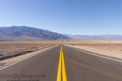 An empty road running straight through Death Valley