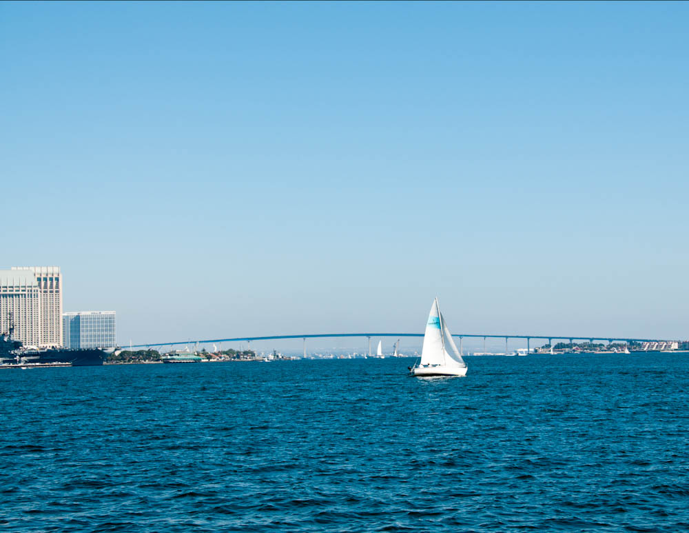 Sailboat in San Diego bay with Coronado bridge in background.
