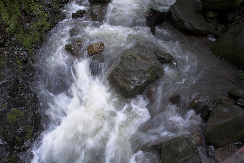 Water flowing below a small bridge.