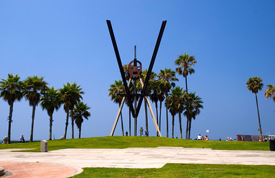 Between the Boardwalk and the beach, (over the grassy hill) is Metal Art amongst the many tall Palm trees at the Venice Beach Park  Venice Beach  July, 2007