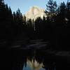 Half dome reflected in the river with a silhouette of the forest.