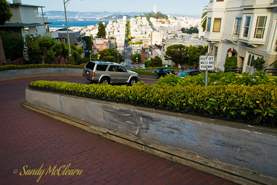 This portion of Lombard Street is so steep that it has to wind back and forth in switchbacks, as otherwise the slope would be too steep for motor vehicles. The rest of Lombard Street stretches off into the background, with Coit Tower on the hill to the right. I didn't notice it at the time, but I have to wonder who the sign is instructing to stay off both the walls AND the roadway, and how they are supposed to read the sign in the first place if they are following instructions.